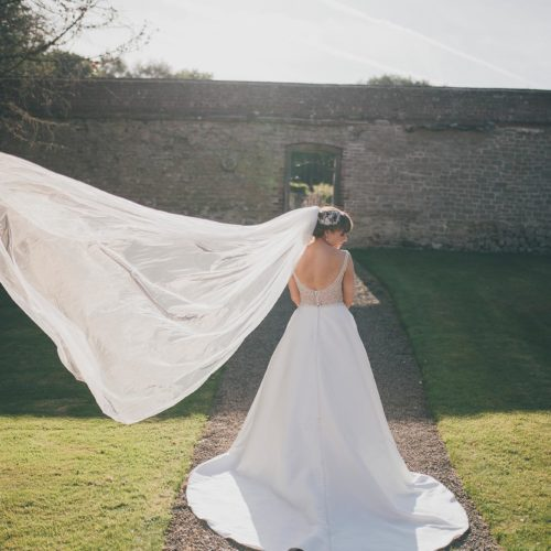 A bride\'s veil floats in the breeze in the garden at Homme House
