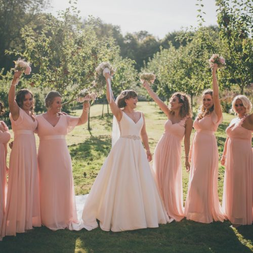 Bride and bridesmaids holding bouquets aloft in group photograph in walled garden orchard