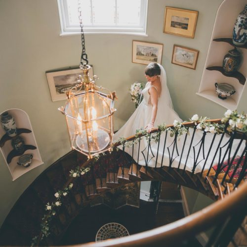Bride descending spiral staircase at Home House