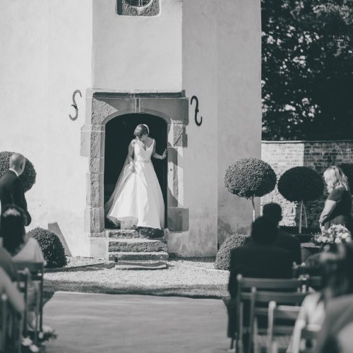 Bride emerging from Summerhouse during wedding ceremony