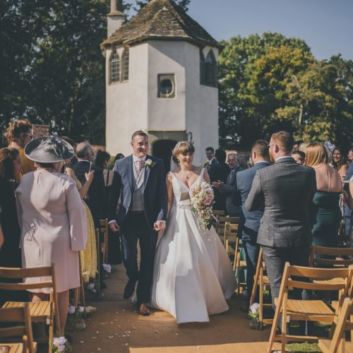 Bride and groom walking down aisle at the end of a walled garden ceremony