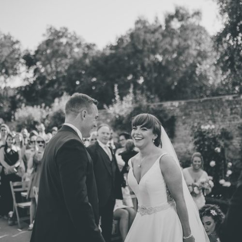 Bride and groom laughing during a Walled Garden ceremony at Homme House