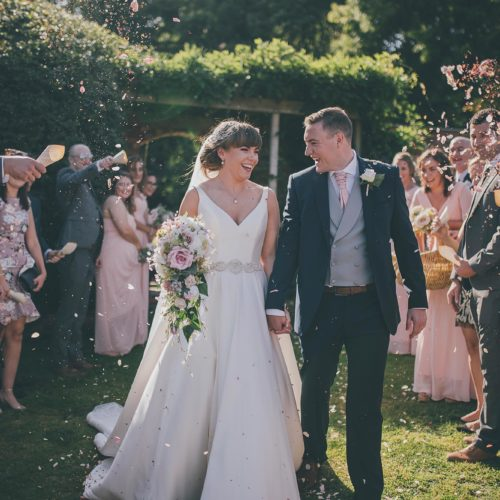 A bride and groom being showered with confetti in the walled garden at Homme House