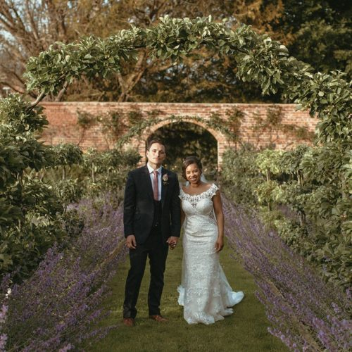 A bride and groom in the evening light on the espalier walk at Homme House