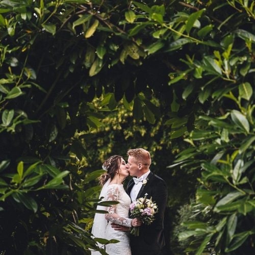 Bride and groom seen kissing through a laurel arch at Homme House