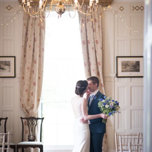 A wedding couple kiss in the Panelled Room at Homme House