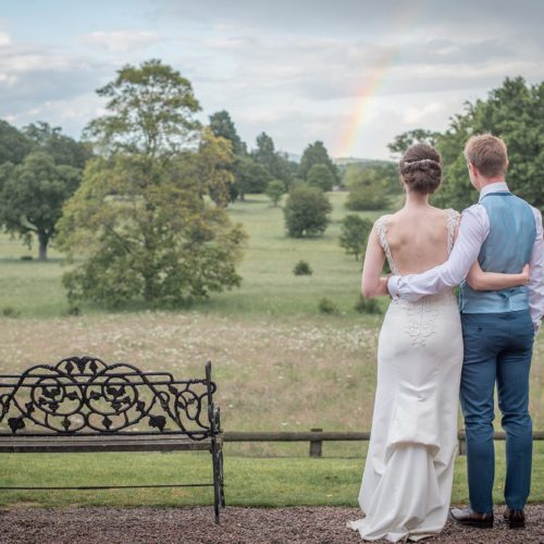 Bride and groom looking out over Homme House\'s historic parkland at a rainbow