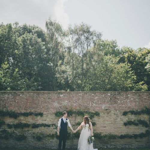 Bride and groom photograph in front of espaliered pears in the walled garden