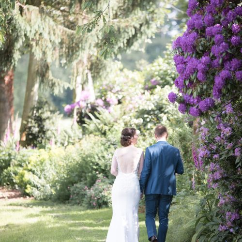 A bride and groom walk past rhododendrons in bloom at Homme House