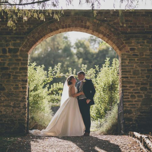 Bride and groom embracing under the archway entrance to the Walled Garden at Homme House