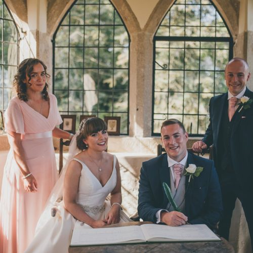 Bride, groom and witnesses during the signing of the register for a Summerhouse wedding ceremony