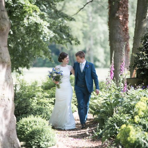 A bride and groom walk through a woodland glade at Homme House