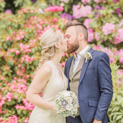A wedding couple kissing in front of rhododendron in bloom at Homme House