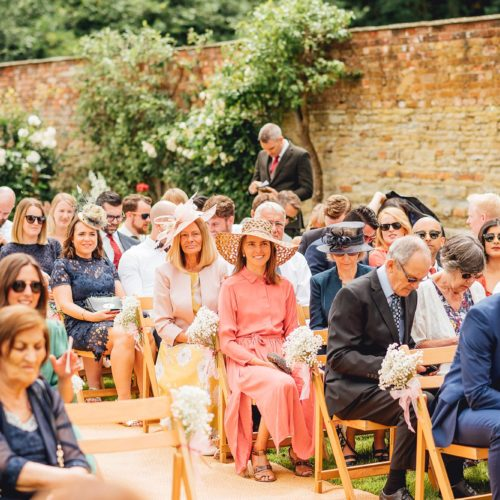 Guests awaiting the start of a walled garden wedding ceremony