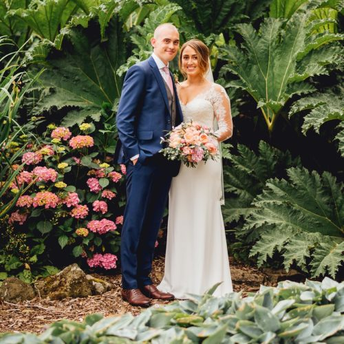 A wedding couple pose in front of huge gunnera at Homme House