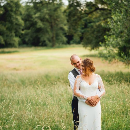 A wedding couple embrace in parkland at Homme House