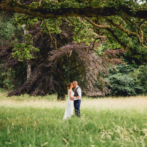 A wedding couple kiss in Homme House\'s historic parkland