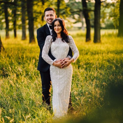 A bride and groom pose in a parkland woodland copse