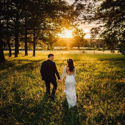 A wedding couple walk in Homme House\'s parkland grass in evening sunshine