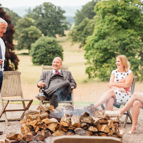Guests relax in front of fire bowls outside Homme House