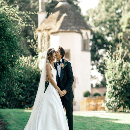 A groom kissing his bride in the Walled Garden at Homme House