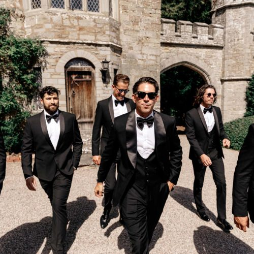 Groom and groomsmen in black tie outside the Tower wing of Homme House