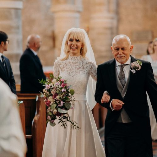 A bride walks the aisle with her father at church