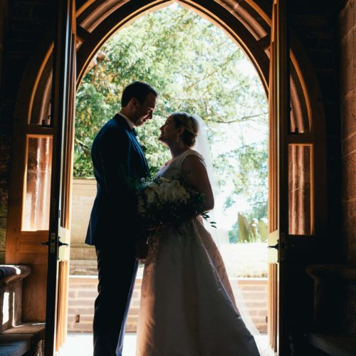 A bride and groom in a church porch