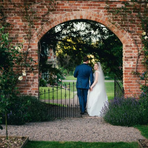 A bride and groom leaving a walled garden