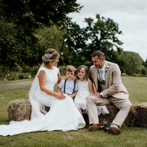 Bride, groom and children on hay bales on the lawn at Homme House