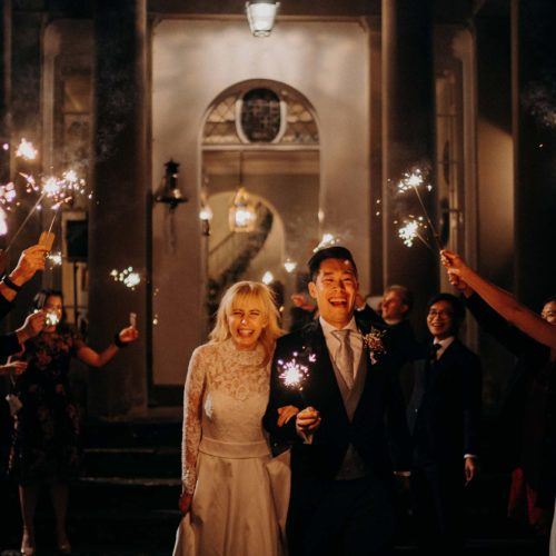 Bride, groom and guests with sparklers outside the front of Homme House in the evening