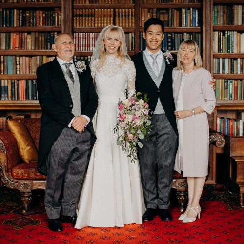 A portrait of wedding couple and parents in the Library
