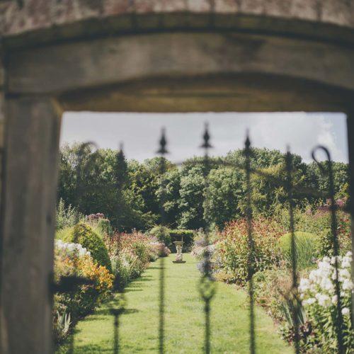 Long flower borders through a gate