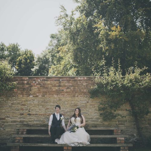 Seated portrait of bride and groom in walled garden
